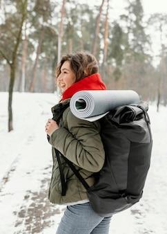 Mulher sorridente com tiro médio e mochila