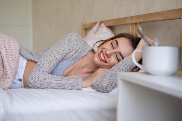 Mulher sorridente com tiro médio na cama