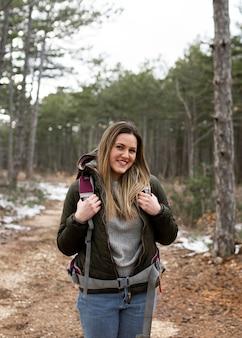 Mulher sorridente com tiro médio na floresta