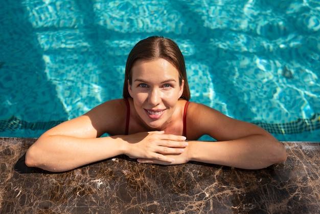 Mulher sorridente com tiro médio na piscina