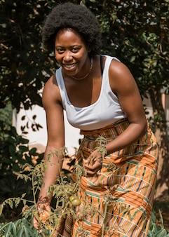 Mulher sorridente com tiro médio no jardim