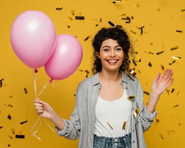 Mulher sorridente com tiro médio segurando balões