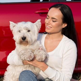 Mulher sorridente com tiro médio segurando cachorro