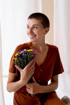 Mulher sorridente com tiro médio segurando flores