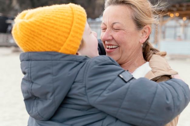 Mulher sorridente com tiro médio segurando menino