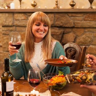 Mulher sorridente com tiro médio segurando o prato