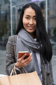 Mulher sorridente com tiro médio segurando o telefone