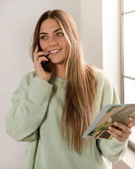Mulher sorridente com tiro médio segurando panfletos