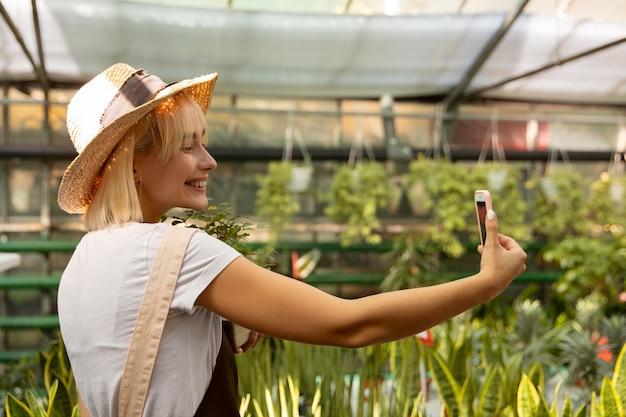 Mulher sorridente com tiro médio tirando uma selfie