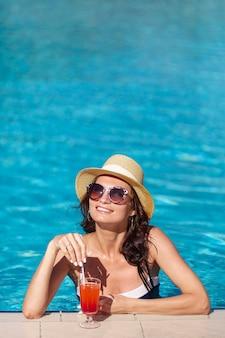 Mulher sorridente com um cocktail sentado na piscina