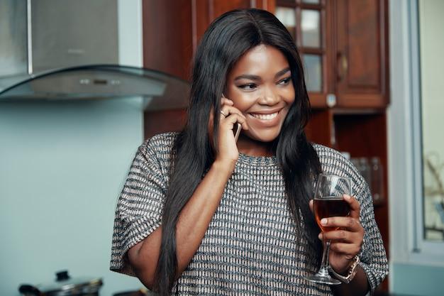 Mulher sorridente com um copo de vinho, falando no telefone