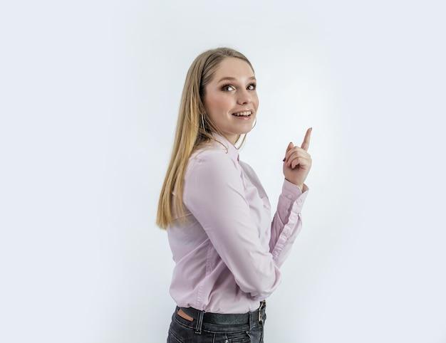 Mulher sorridente com um dedo apontando para cima
