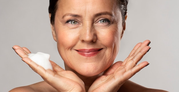 Mulher sorridente com um limpador espumante na mão