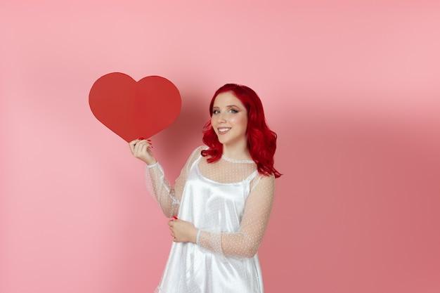 Mulher sorridente com um vestido branco e cabelo ruivo abraça um grande coração de papel vermelho