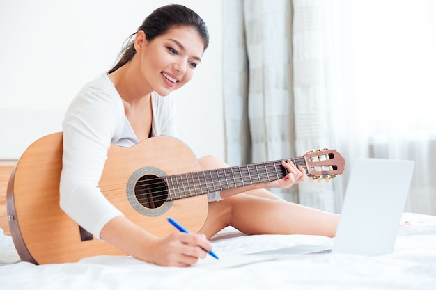 Mulher sorridente com um violão, sentada na cama e fazendo anotações no bloco de notas