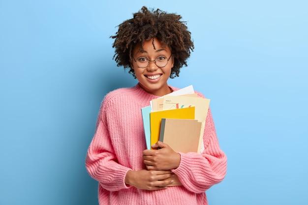 Mulher sorridente com uma afro posando com um suéter rosa