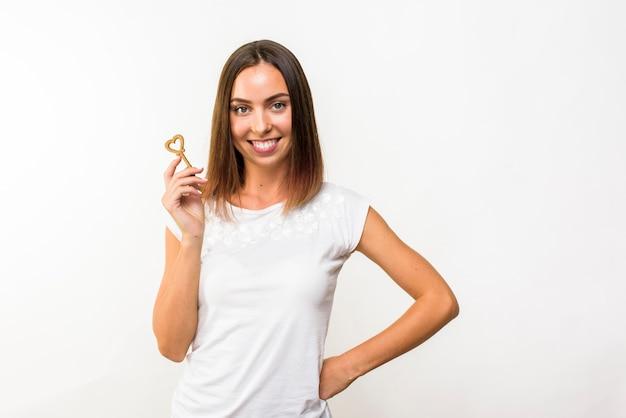 Mulher sorridente com uma chave em forma de coração
