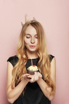 Mulher sorridente, com uma coroa, segurando um bolo de aniversário