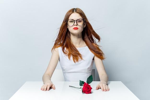 Mulher sorridente com uma flor rosa nas mãos, mesa de trabalho, emoções, presente luxo