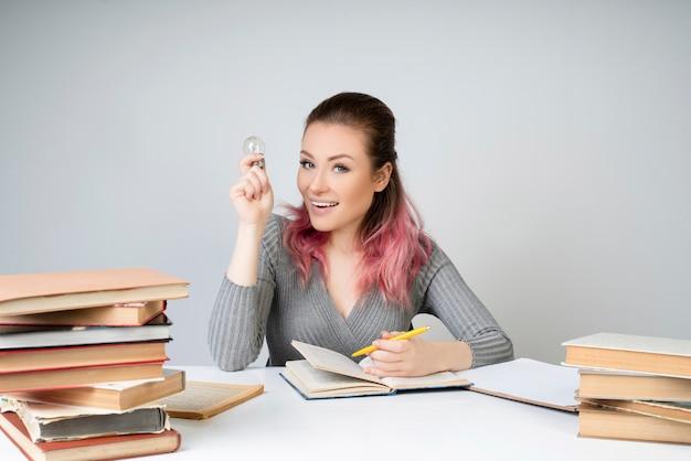 Mulher sorridente com uma lâmpada e lápis amarelo nas mãos