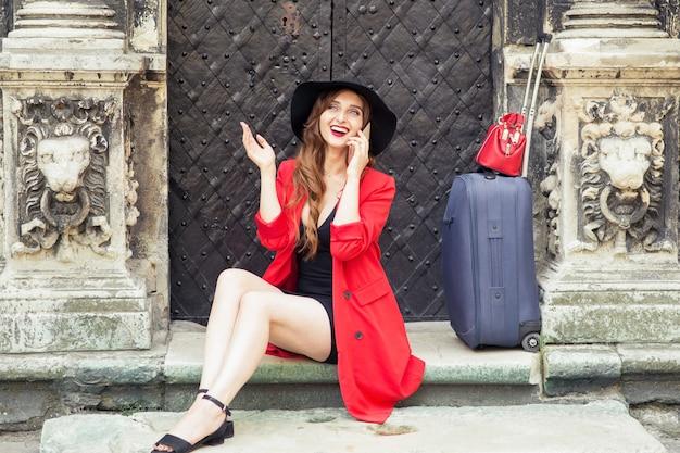 Mulher sorridente com uma mala está falando pelo smartphone nas escadas perto da porta antiga.