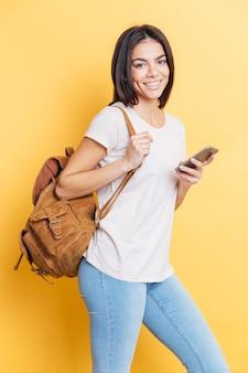 Mulher sorridente com uma mochila segurando um smartphone e olhando para a frente na parede amarela
