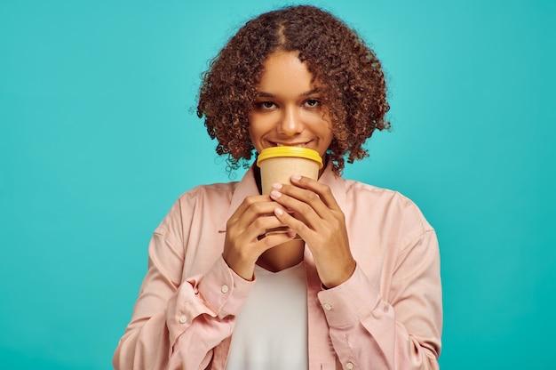 Mulher sorridente com uma xícara de café, parede azul, emoção. expressão facial, pessoa do sexo feminino olhando para a câmera no estúdio, conceito emocional, sentimentos