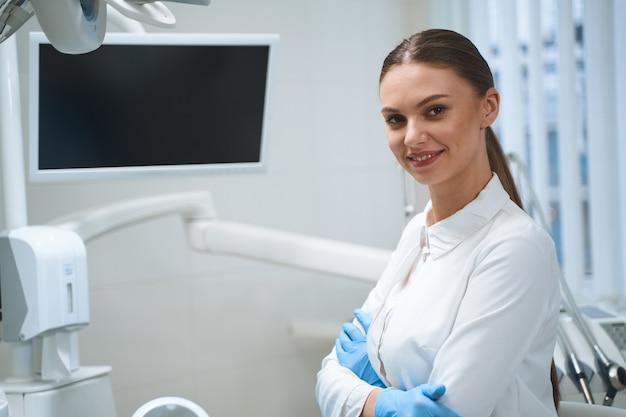 Mulher sorridente com uniforme branco e luvas esterilizadas está em uma clínica odontológica moderna perto de uma tela digital
