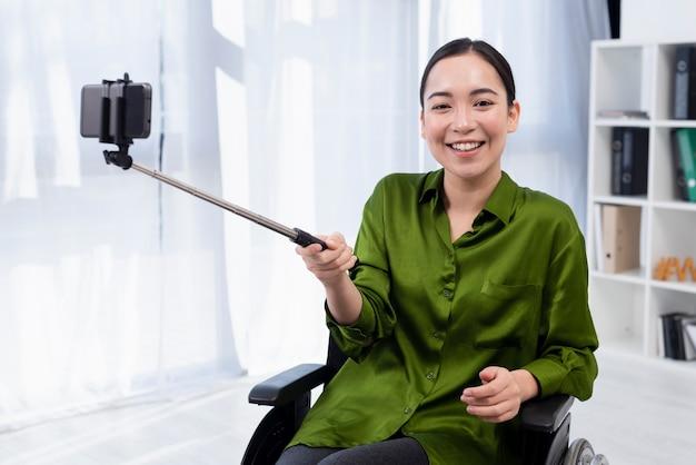 Mulher sorridente com vara de selfie