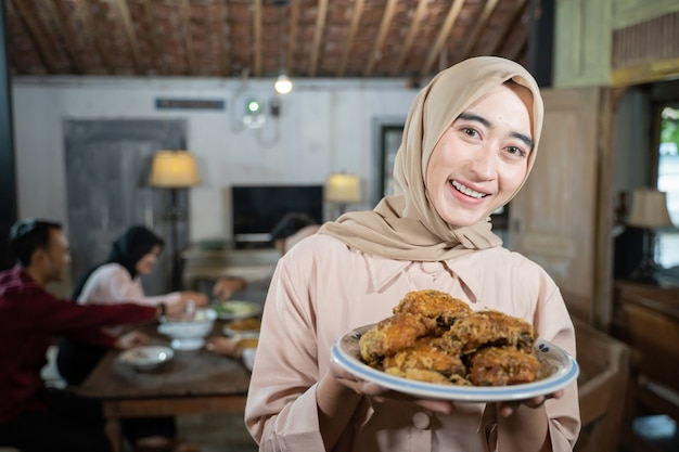 Mulher sorridente com véu carregando um prato de frango frito com membros da família comendo juntos