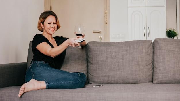 Mulher sorridente com vinho e controle remoto