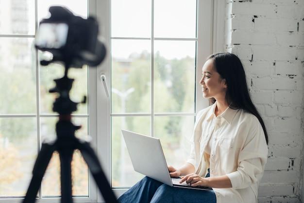 Mulher sorridente com visão lateral fazendo um vlog