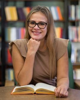 Mulher sorridente com vista frontal e livro