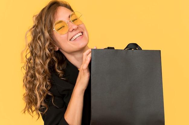 Mulher sorridente com vista frontal e sacola de compras preta
