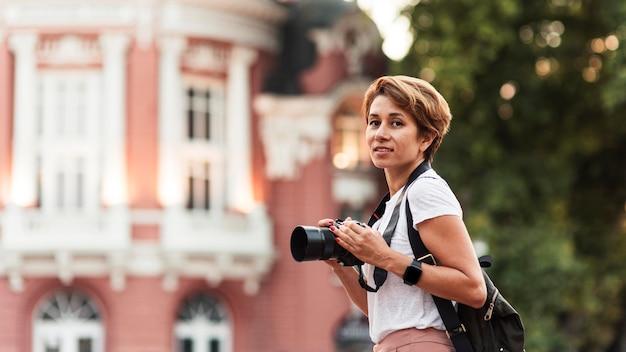 Mulher sorridente com vista lateral e câmera fotográfica