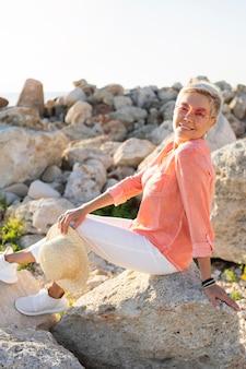 Mulher sorridente com vista lateral posando sobre pedras