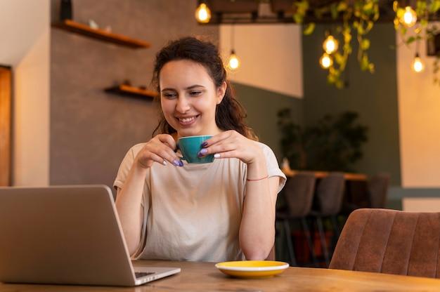 Mulher sorridente com xícara e laptop