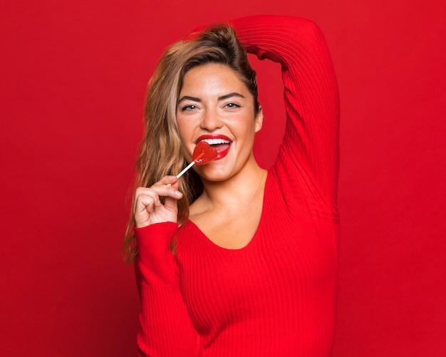 Mulher sorridente comendo pirulito