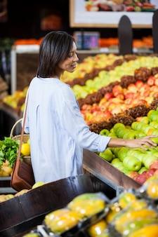 Mulher sorridente comprando frutas na seção orgânica