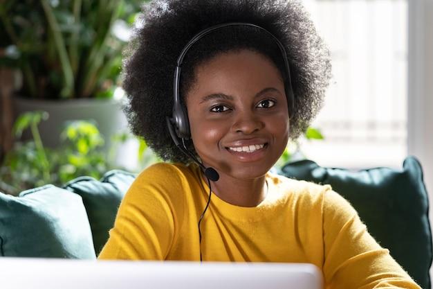Mulher sorridente, consultora afro-americana, usa fones de ouvido