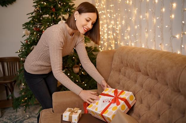 Mulher sorridente contando o presente de natal no sofá da sala perto da árvore de natal