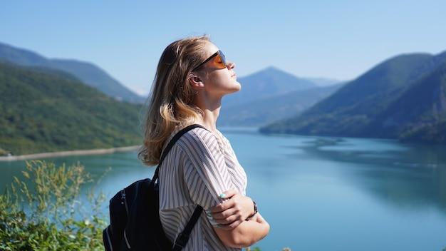 Mulher sorridente contra a paisagem montanhosa e o lago. paisagem do lago de reservatório zhinvali com montanhas. a principal cordilheira do cáucaso.