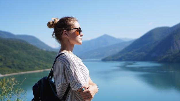 Mulher sorridente contra a paisagem montanhosa e o lago