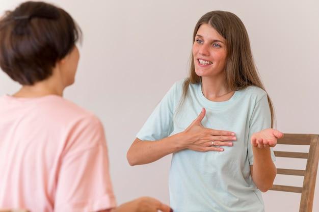 Mulher sorridente conversando com alguém usando a linguagem de sinais