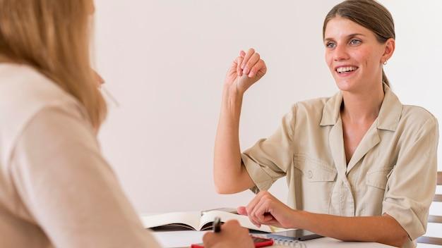 Mulher sorridente conversando com um amigo usando linguagem de sinais