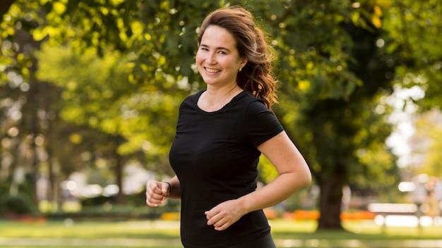 Mulher sorridente correndo em roupas esportivas