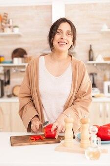 Mulher sorridente cortando ingredientes alimentares na cozinha. esposa cortando pimentão vermelho. linda alegre feliz sorridente mulher na sala iluminada, preparando uma refeição saudável e orgânica.