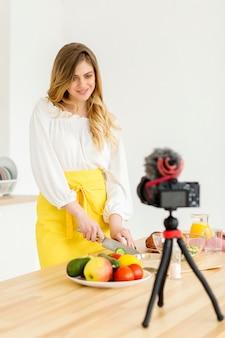 Mulher sorridente cortar legumes
