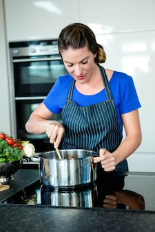 Mulher sorridente, cozinhar vegetais em uma panela no fogão