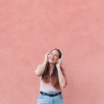 Mulher sorridente curtindo música em fones de ouvido